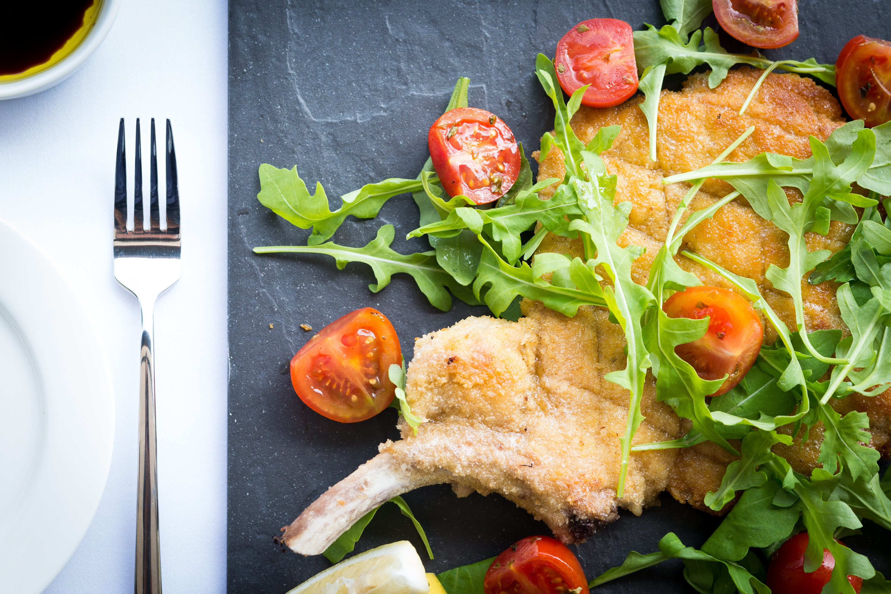 Spasso - Cotoletta alla Milanese pork chop Milanese Elephant ear with rocket salad and cherry tomatoes